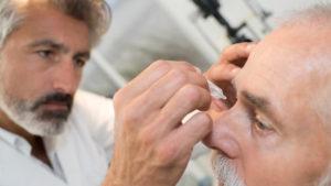 Ein Augenarzt bereitet einen Patienten auf die Glaukom Untersuchung vor