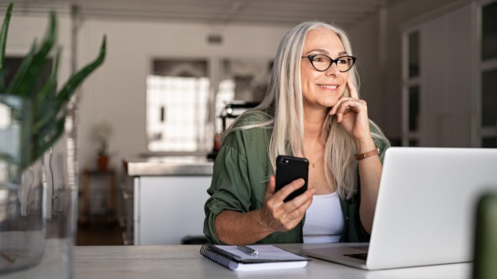 Eine Frau mit einer Gleitsichtbrille und einem Smartphone