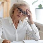 Eine Frau sitzt am Computer und denkt angestrengt nach