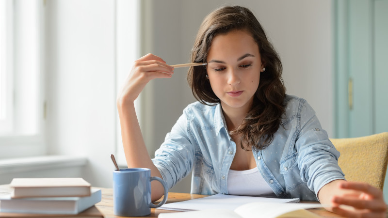 Eine junge Frau arbeitet konzentriert am Schreibtisch