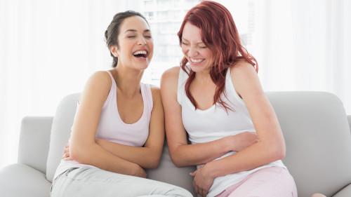Zwei Frauen sitzen auf der Couch und lachen laut