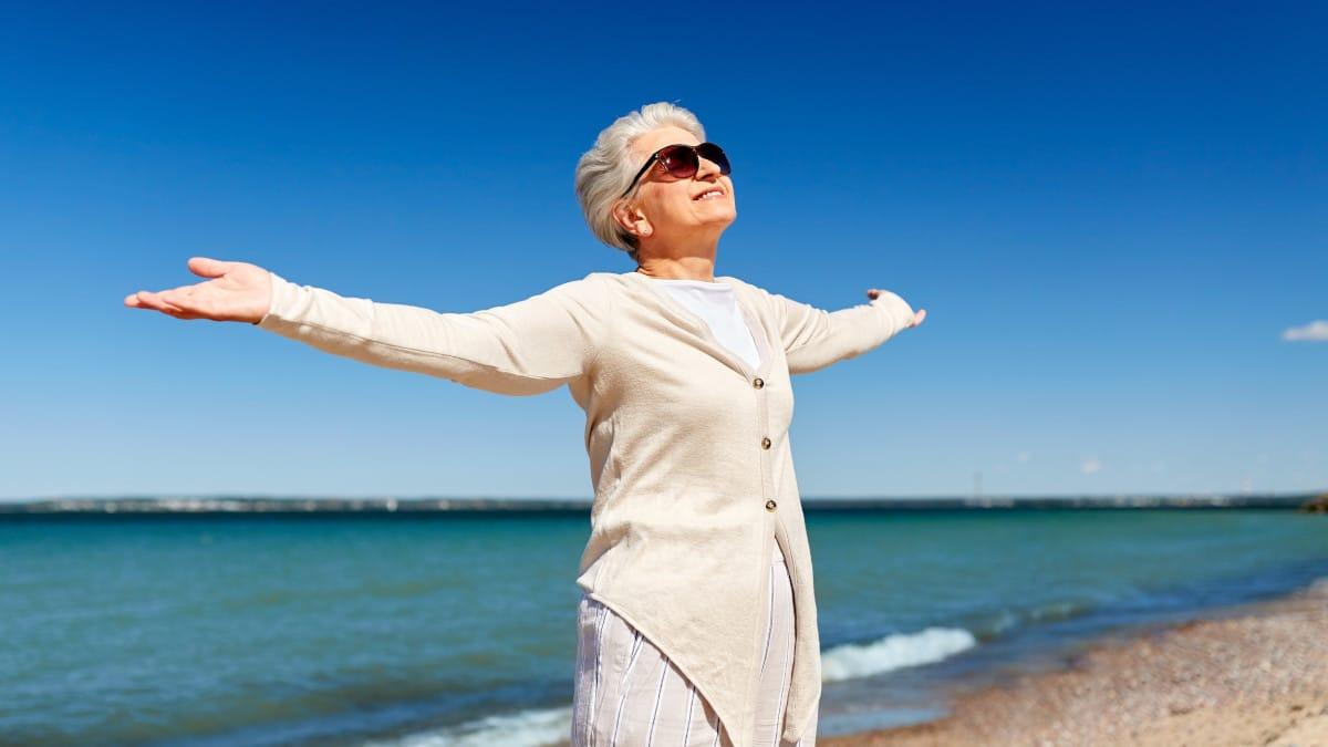 Eine Frau mit Sonnenbrille breitet die Arme aus