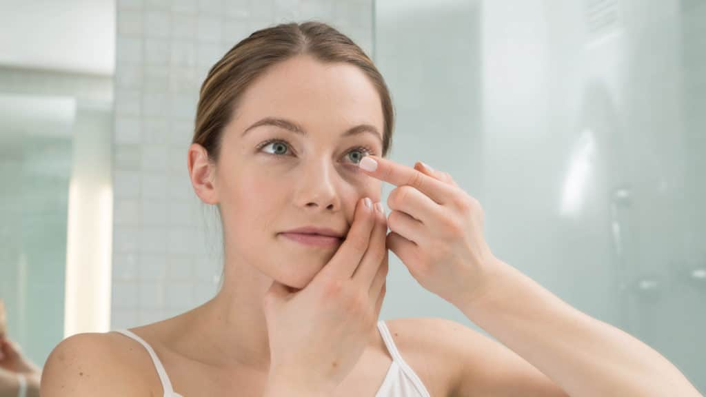 Frau setzt sich eine Kontaktlinse ins Auge