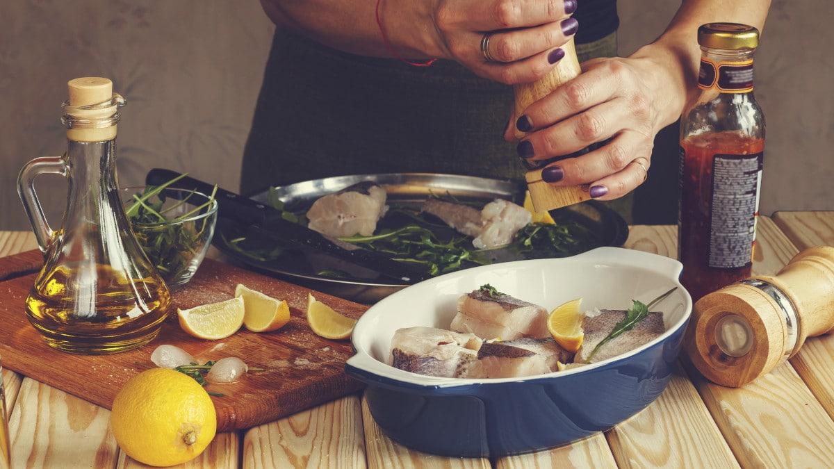 Frau würzt ein Fischgericht für eine gesunde Ernährung bei Multipler Sklerose