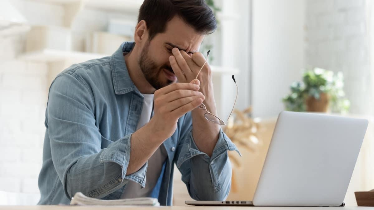 Ein gestresster Mann hält sich die Hand vor das Gesicht