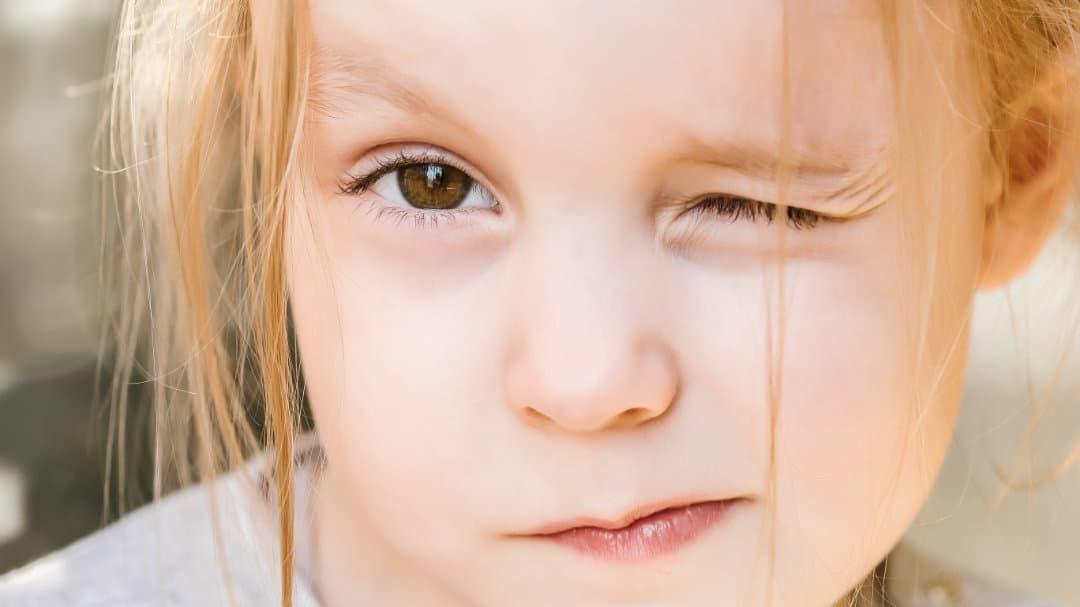 Ein Mädchen schaut in die Kamera und kneift die Augen zusammen
