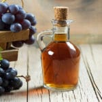 Eine Flasche Traubenessig steht auf einem Holztisch umgeben von Weintrauben