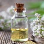 Eine Flasche mit Baldrianöl steht auf einem Tisch umgeben von Blüten der Pflanze