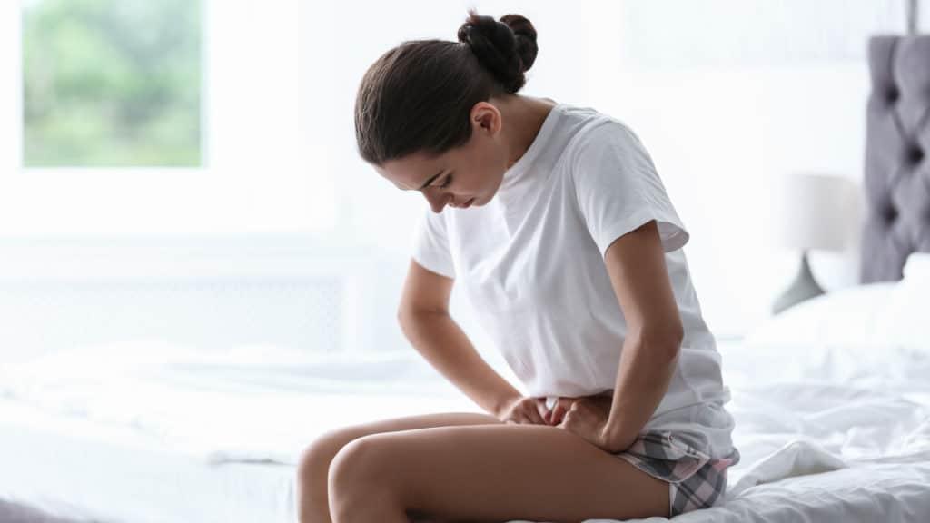 Eine Frau mit einer Blasenentzündung drückt ihre Hände in den Schoss