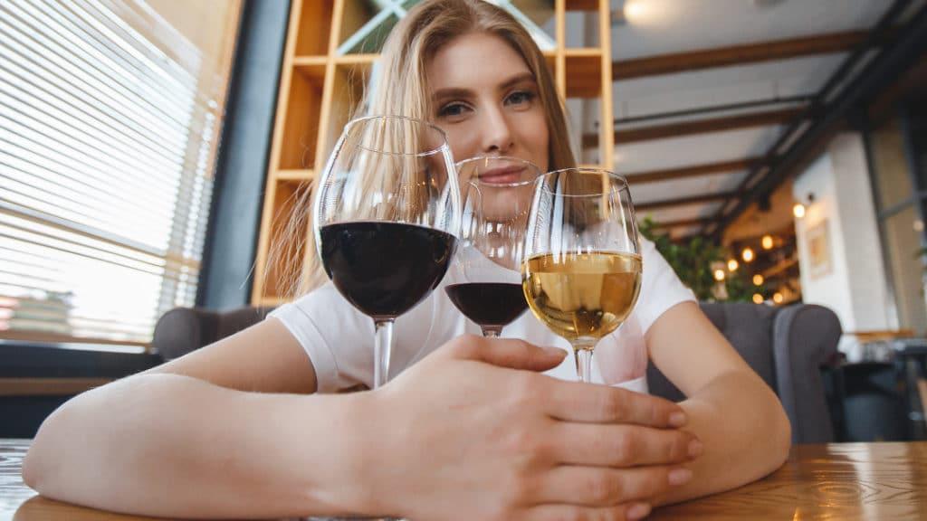 Eine Frau sitzt an einem Tisch vor drei Gläsern Wein