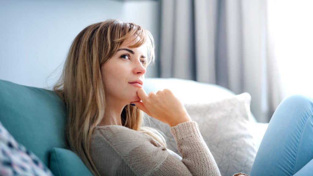 Eine Frau sitzt auf der Couch und denkt nach