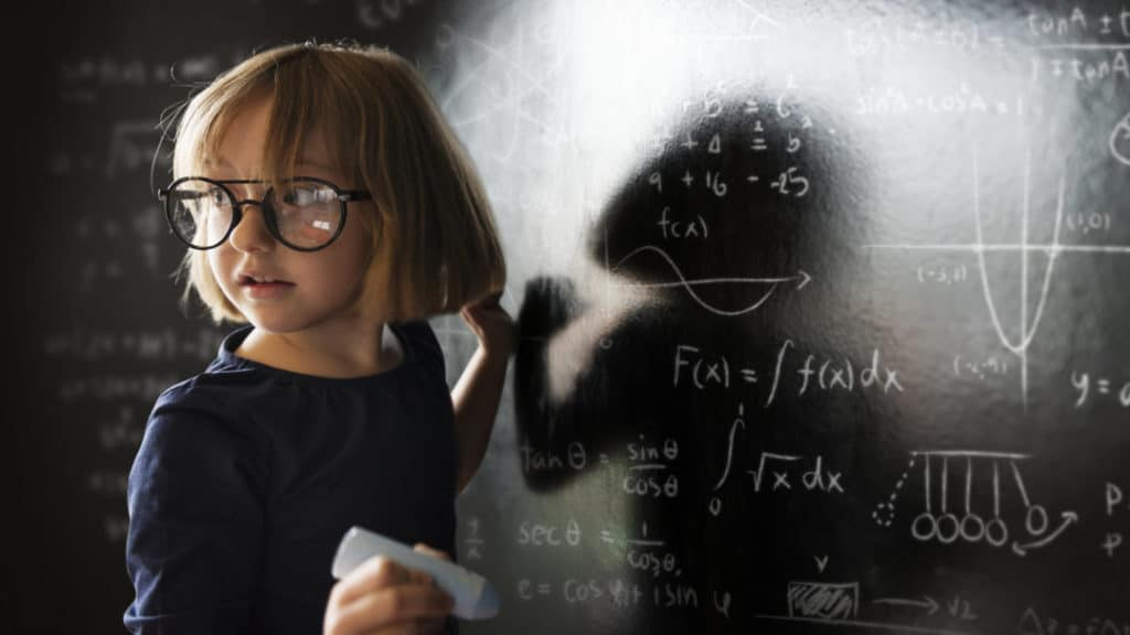 Ein Mädchen löst schwierige Aufgaben an einer Tafel - ein echtes Genie