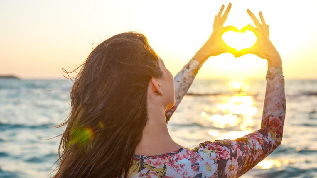 Eine Frau formt mit den Händen ein Herz und rahmt damit die Sonne ein