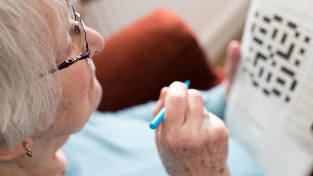 Eine Seniorin löst ein Kreuzworträtsel in der Zeitung