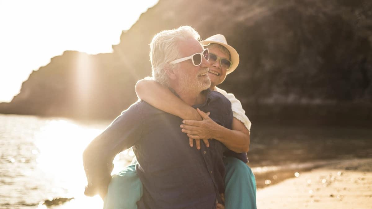 Zwei Senioren schützen Ihre Augen mit Sonnenbrillen vor der grellen Sonne am Strand