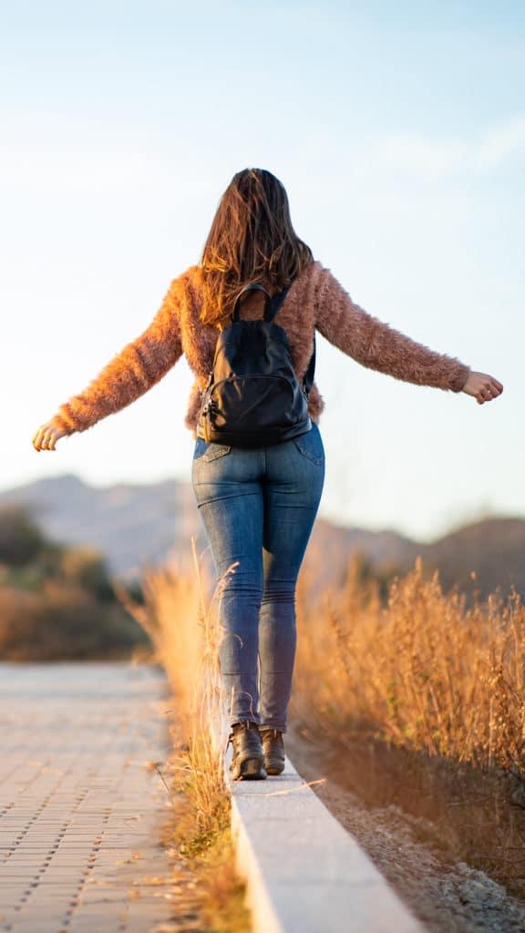 Eine Frau spaziert bei schönem Wetter an einer Straße entlang