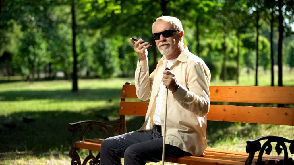 Ein Sehbehinderter Mann sitzt auf einer Parkbank und nutzt sein Smartphone
