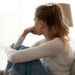 Eine junge Frau sitzt am Fenster und grübelt