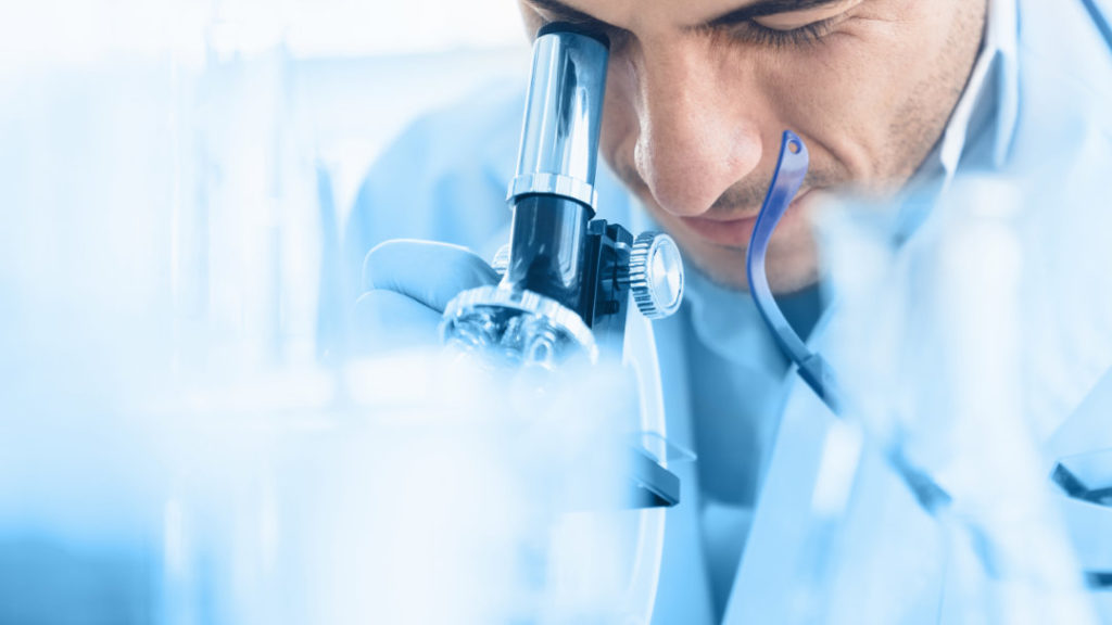 Ein Wissenschaftler schaut durch ein Mikroskop